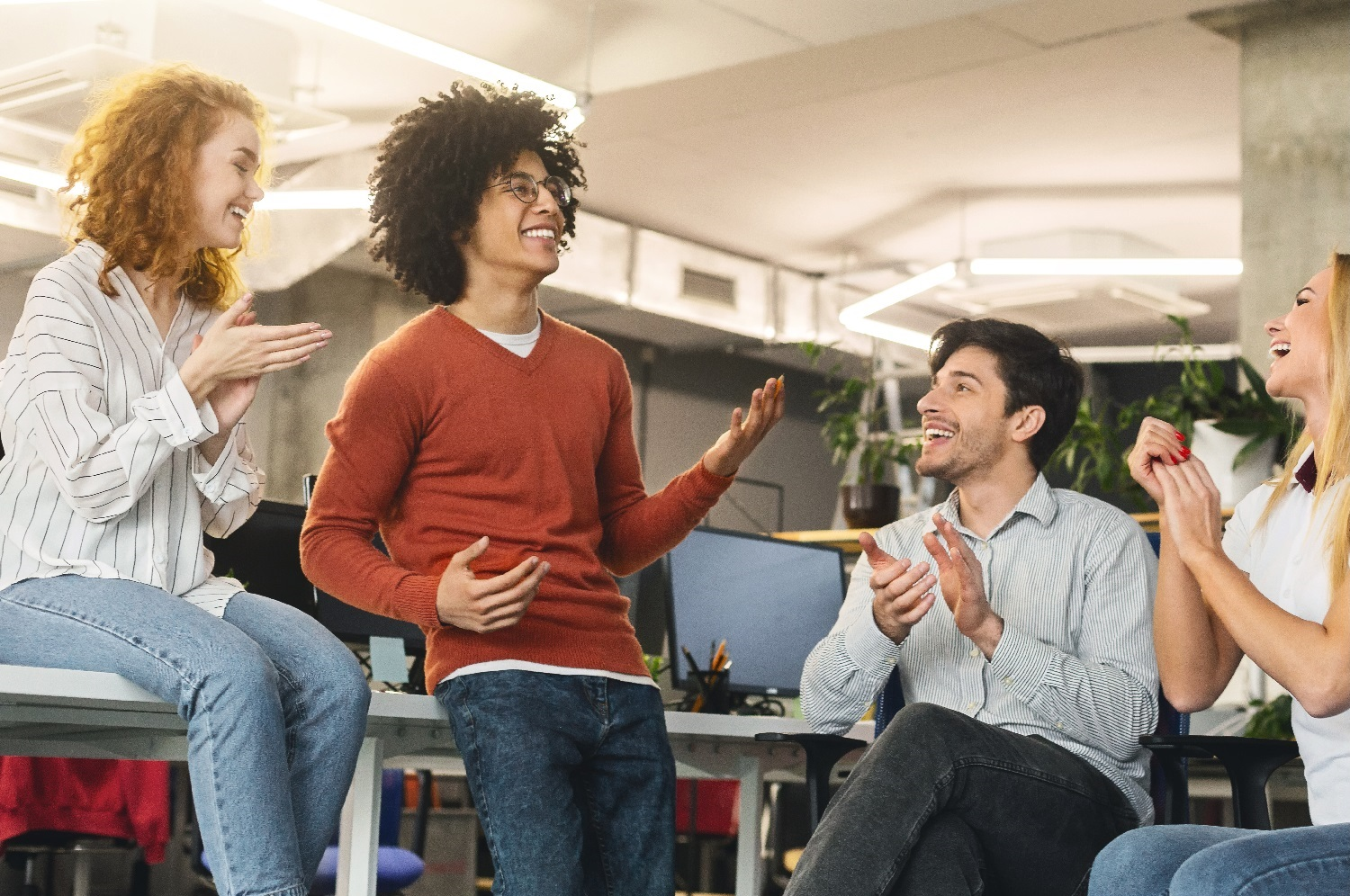 Cheerful business team greeting their colleague, applauding to successful black guy, free space