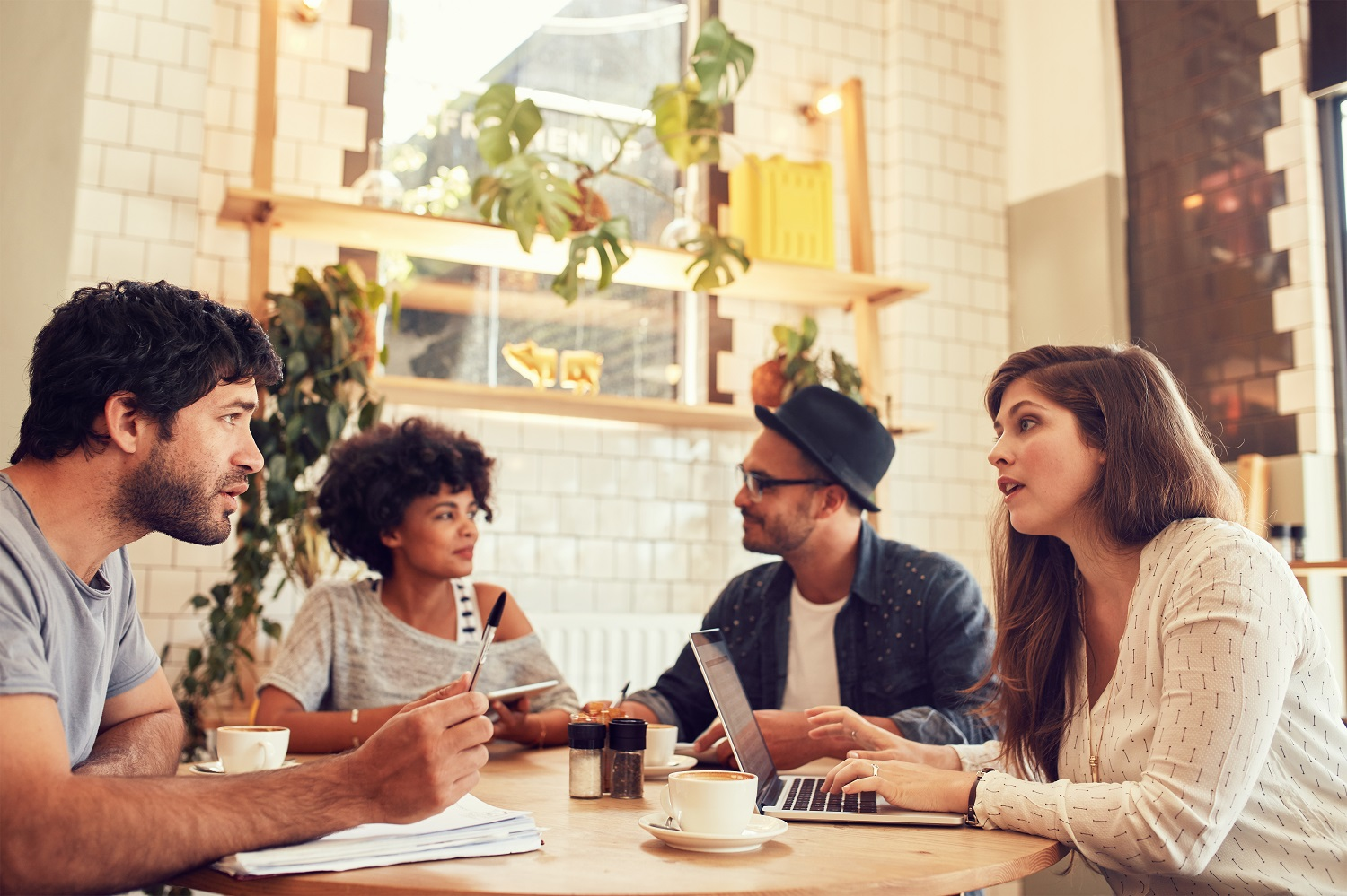 Portrait of young people sitting in a coffee shop with laptop and talking. Young men and women discussing business ideas at a cafe.